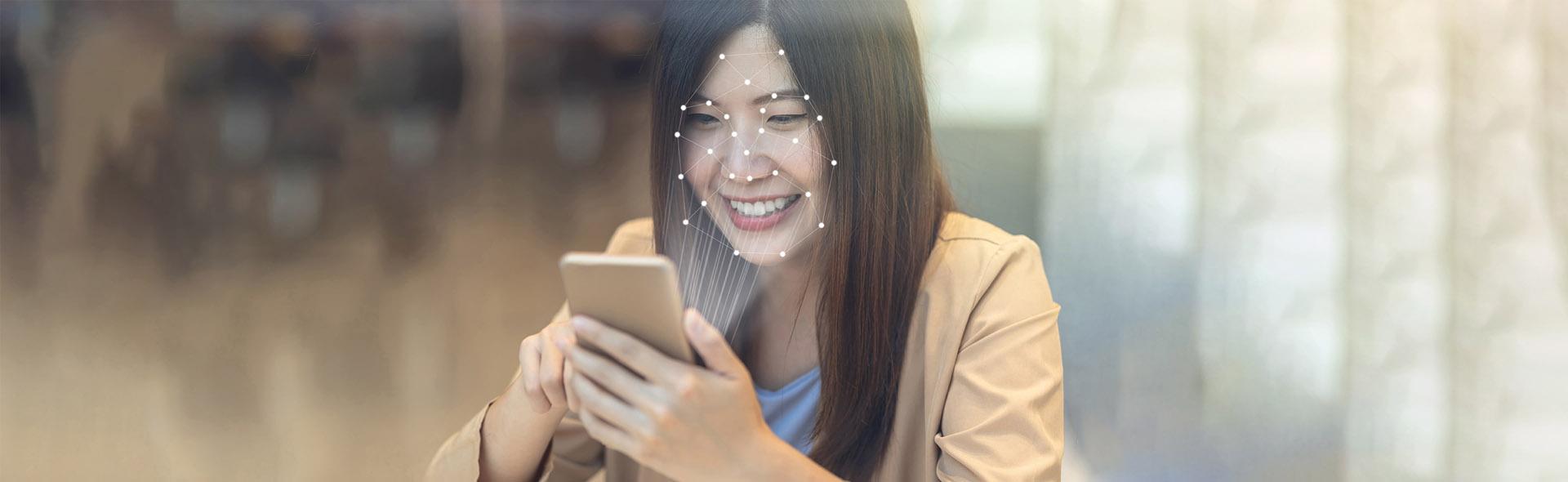 Frau mit Handy, welches ihr Gesicht scannt