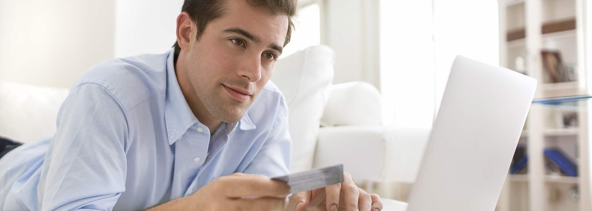 Mann mit Kreditkarte und Laptop